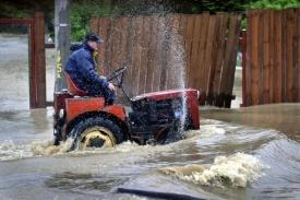 Muž vyráží traktorem na pomoc sousedům.