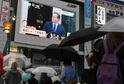 Lidé v Tokiu sledují Cameronovo prohlášení o rezignaci.