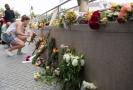 Lidé nosí květiny k provizornímu památníku poblíž místa střelby.