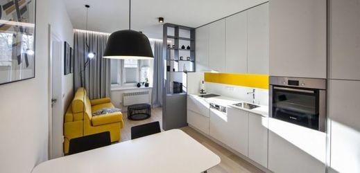 Kuchyně navržená na míru působí díky použitým barvám a materiálům jednoduše a dokonale splývá s obývací částí bytu.