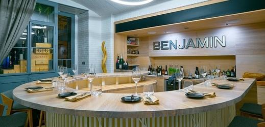 Interiéru dominuje masivní dřevěný stůl, u kterého stolují všichni hosté pohromadě.