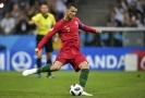 Christiano Ronaldo právě posílá míč přes zeď přesně do sítě.