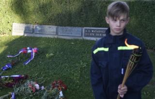 Dobrovolný hasič na čestné stráži u hrobu rodiny Masaryků.