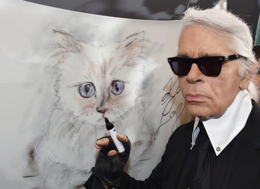 """Karl Lagerfeld stojí vedle kresby své kočky Choupette na vernisáži pro svůj kalendář """"Corsa Karl a Choupette"""" v Palazzo Italia v Berlíně."""