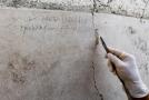 Nápis uhlem na zdi, který archeologové nalezli v neprobádané části antického přístavu.
