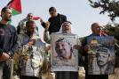 Palestinci drží fotografie Jásira Arafata při výročí 14 let od jeho úmrtí.