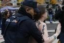 Policista zadržuje členku hnutí Femen na manifestaci v Madridu.