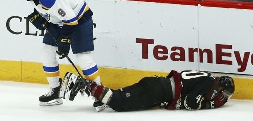 Michael Grabner leží na ledě po zásahu hokejkou do obličeje.