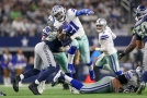 Ezekiel Elliott z Dallasu Cowboys se snaží proskočit mezi obránci.