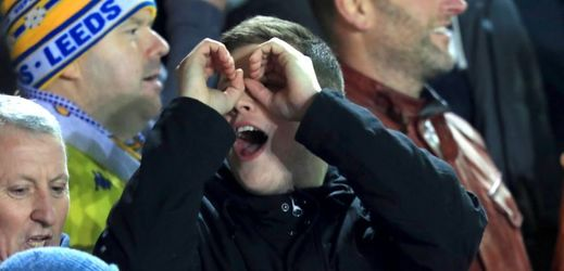 Mladý fanoušek napodobuje špehování během zápasu Leeds-Derby County.