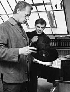 Jiří Suchý a Jiří Šlitr (vlevo) diskutují nad gramofonovou deskou ve Šlitrově ateliéru na pražských Vinohradech, 1965.