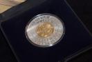 Pamětní mince s portrétem prvního ministra financí Aloise Rašína. Z druhé strany je zlatá inlej s replikou československé korunové mince z roku 1922.
