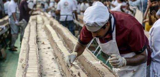Jeden z indických cukrářů při práci na dortu.