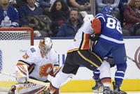 Brankář Calgary Flames David Rittich (33), Mark Giordano (5) a hokejista Toronta William Nylander (88).