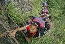 Děti lezoucí po žebříku do svých domovů na útesu.