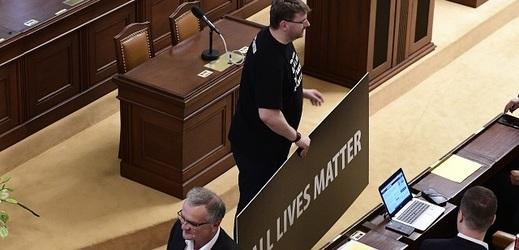 Poslanec Lubomír Volný (držící transparent).