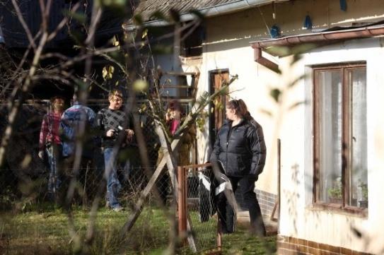 Tauchenova teta vstupuje s vyšetřovateli do jeho domu.