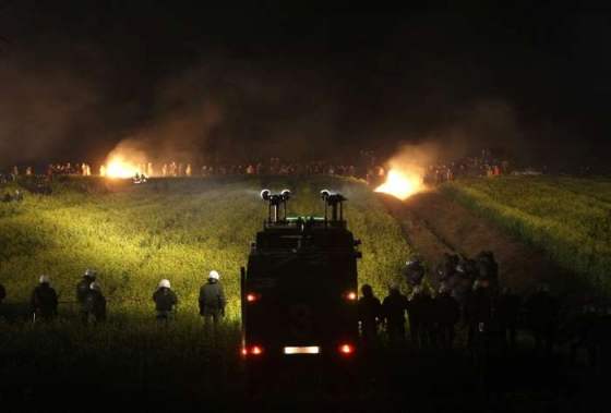 Krajinu před bitvou osvětlují hořící balíky slámy zapálené aktivisty.